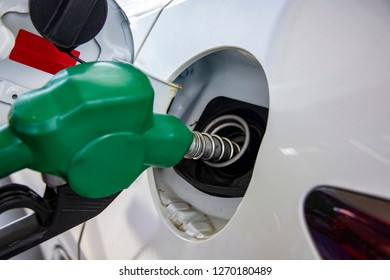Green Handle pumping gasoline fuel nozzle to refuel. Vehicle fueling facility at petrol station. White car at gas station being filled with fuel. Transportation and ownership concept.