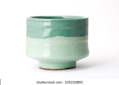 Green handmade pottery cup on white background