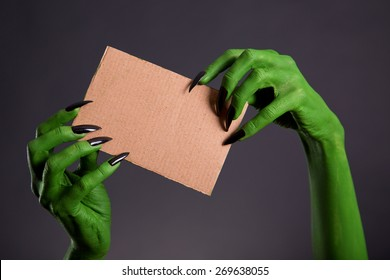 Green hands with long black nails holding empty piece of cardboard, Halloween theme