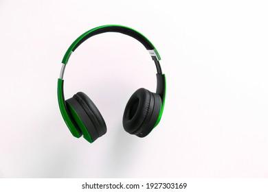 Green headphone isolate on white background.
