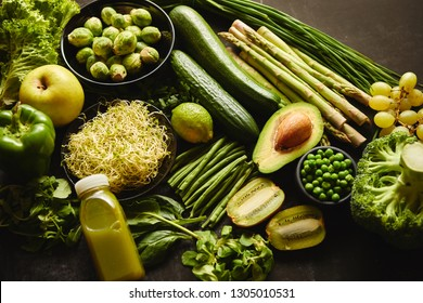 Green healthy food composition with avocado, broccoli, apple smoothie cucomber asparagus kiwi bean. Placed on dark background. Top view.