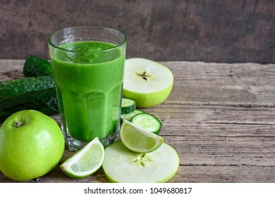 green healthy smoothie in a glass with spinach, apple, cucumber and lime over rustic wooden table. detox drink. close up