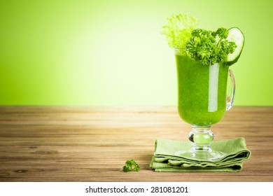 Green healthy smoothie juice with vegetables on wooden table against green background with copy space
