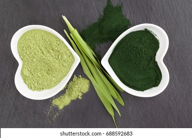 Green healthy superfood powder from above on black surface. Spirulina and chlorella.