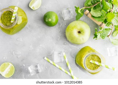 Green healty drink in mason jar with green apple, mint, lime and melting ice cubes on grey background. Vegetarian food concept. Detox. Text space