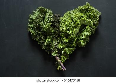 Green heart made of kale leaves on blackboard background. Go green
