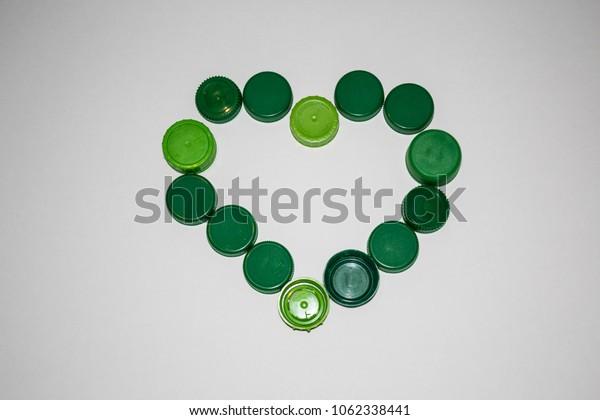 green heart shape made of bottle caps