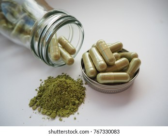 Green herb Gingko extract powder & Ginkgo biloba medicine capsule & supplement on the lid cover of glass bottle on white background, Natural herbal use for prevention sore throat and treatment fever.