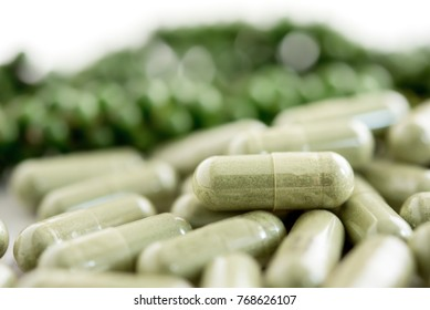 Green herbal extract capsules in front of bitter melons against white table background for diet supplementation and good health, extreme closeup