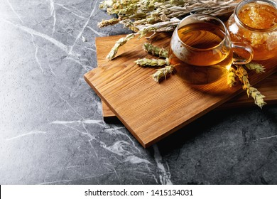 Green herbal Greek mountain tea in glass cup served with honey over dark texture background