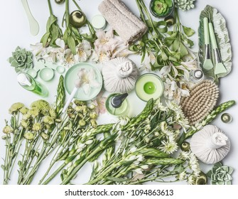 Green herbal spa setting with water bowl, flowers, candle, massage  balls, cosmetic products, herbs and flowers on white background, top view. Beauty,  healthy lifestyle and wellness concept