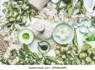 Green herbal spa setting with water bowl, flowers, candle, massage  balls, cosmetic products, herbs and flowers, top view. Beauty,  healthy lifestyle and wellness concept