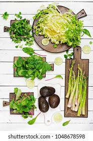 Green herbs, asparagus and black avocado on a white wooden background. Top view. Flat lay