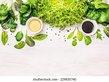 green herbs mix salad with dressing, preparation on white wooden table, food background with place for text