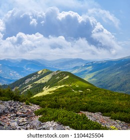 green hill among a rocky mountain under a dense clouds