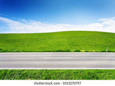 Green hill and asphalt road, side view. Landscape in summer day