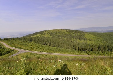 Green hill with a road under the blue sky in summer.