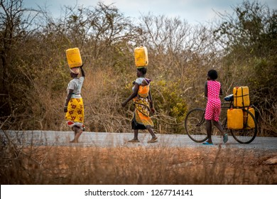 Green Hill School, Tsavo East, Kenya - August 2018: Black African women carrying big yellow tanks of water to their village.