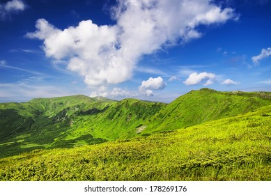 Green hills and cloudy sky. Beautiful summer landscape