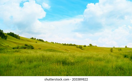 Green hills and field against a beautiful sky Green hills and field against a beautiful sky
