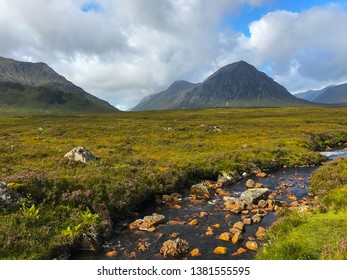 The green hills, fields and mountains  of Glen Coe West Highlands in Scotland, United Kingdom with stream in the foreground