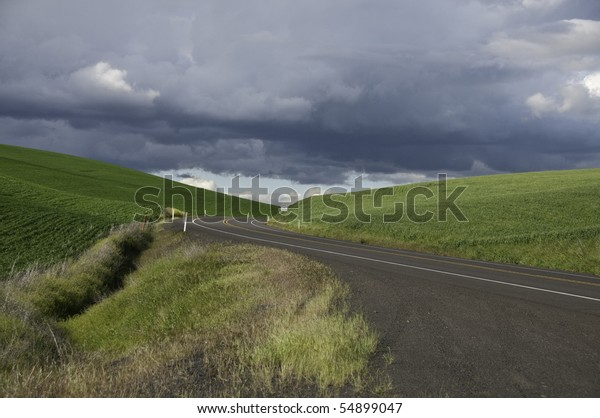 Green hills with road going through. Dark rain clouds coming.