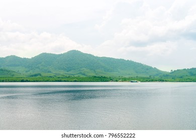 Green hilly tropical island with calm sea and cloudy sky