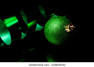 Green holiday decoration and ribbon on a black background