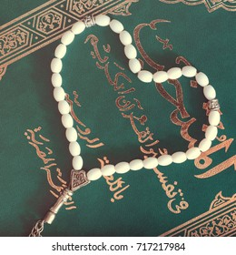 Green Holy Quran Book with white beads in the shape of a heart on a brown wooden background. Prayer Concept. Top view. flat lay. toned