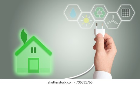 Green home as a symbol of renewable energy and architecture. Business man holding a plug.