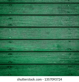 Green horizontal wooden texture for background or mockup. Rustic painted wood texture close up. Barn wall or fence. Flat wood banner, billboard or signboard