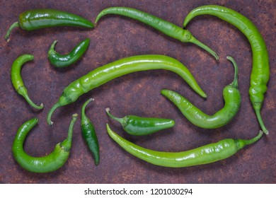 Green hot chilli peppers on dark background. Top view
