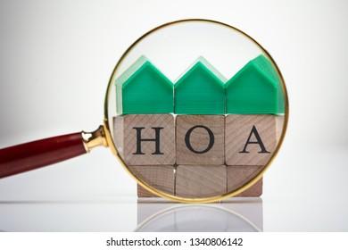 Green House Model Over Homeowner Association Wooden Blocks Seen Through Magnifying Glass