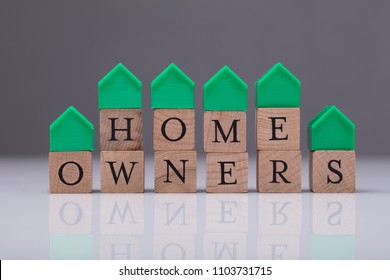 Green House Model Over Wooden Blocks Showing Home Owners Text