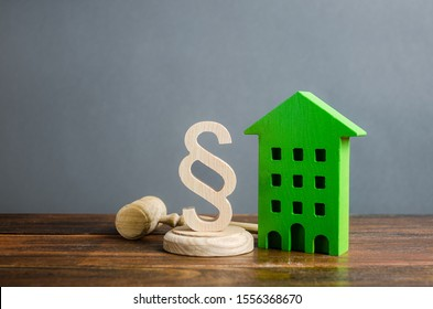 Green house and paragraph figurine with a judge gavel. Concept legislation on residential buildings and infrastructure. Standardization and construction of housing. Real estate legal services.