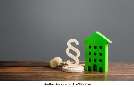 Green house and paragraph figurine with a judge hammer. Litigation in housing and real estate disputes. Norms and rules for construction, maintenance. Encouraging green and energy-saving technologies.