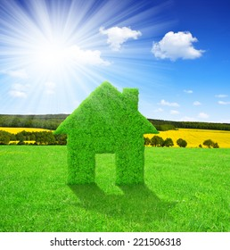 Green house symbol on meadow with sunny sky