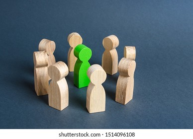A green human figure is surrounded by a circle of people. Cooperation and collaboration. Fundraising and people around the idea. To unite like-minded persons. Leader and leadership skills.