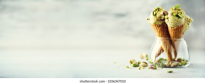 Green ice cream in waffle cone with chocolate and pistachio nuts on grey stone background. Summer food concept, copy space. Healthy gluten free ice-cream. Banner,