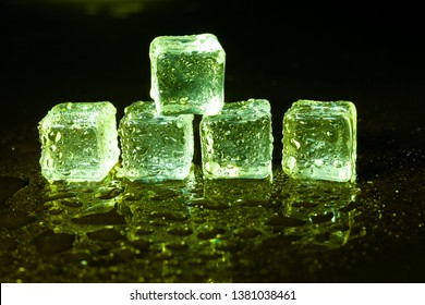 Green ice cubes on black table background.