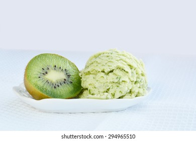 Green ice-cream with kiwi in white porcelain dish over white cloth.