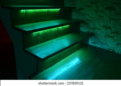Green illuminated wooden stairs and rough stone wall
