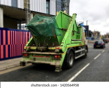 Green industrial skip with sheet cover top, loaded securely on back of truck. Focus on back & side of the metal rubbish bin with blurry surrounding background. Building site removal business concept.