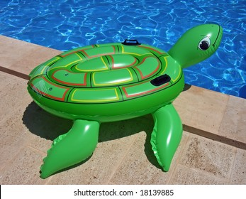 Green inflatable turtle on the edge of a swimming-pool