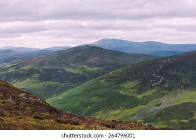 The green irish mountains with the grey cloudy sky