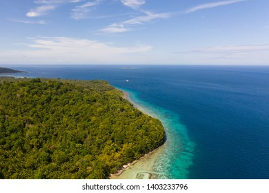 Green island with coral reef. Coast of Camiguin Island, Philippines, view from above. Seascape in sunny weather.