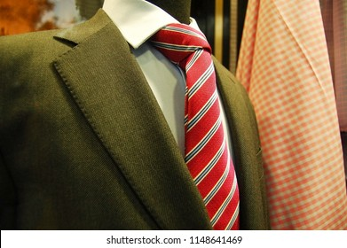 Green jacket with white shirt and red tie with stripes. A sample for dress code.