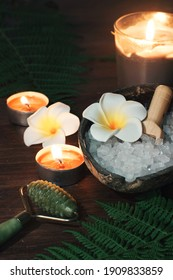 green jade massage roller against the background of turn signals and burning candles on the table.