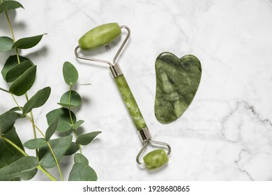 Green jade roller and gua sha stone for facial massage and eucalyptus branch on marble background. Home beauty and selfcare accessories. Face roller for anti age wrinkle treatment. Top view, flat lay.