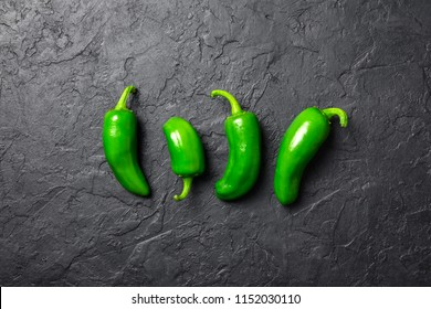 Green jalapeno hot pepper on black background closeup. Food photography